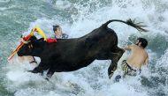 तस्वीरें: समंदर किनारे सांड़ और इंसान की दौड़