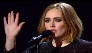 Emotional Adele visits London fire site, comforts victims