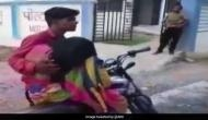 Shocking: Video of a man carrying mother's body on bike for post-mortem in Madhya Pradesh goes viral; probe ordered