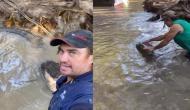 नदी में उतरकर मगरमच्छ के साथ मस्ती करने लगा शख्स, वीडियो में देखें जबड़ा पकड़ने के बाद हुआ क्या?