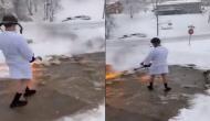 इस शख्स ने निकाला बर्फ हटाने का अनोखा तरीका, वीडियो में देखें हाथ में बीयर और सिगार लेकर किया ये काम