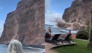 समुद्र किनारे मस्ती कर रहे थे पर्यटक तभी पानी में आ गिरी ऊंची चट्टान, वीडियो में देखें फिर हुआ क्या