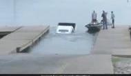 Video: रिपोर्टिंग के दौरान पीछे खड़ी कार डूबने लगी झील में, देखकर रिपोर्टर ने किया हैरान कर देने वाला काम